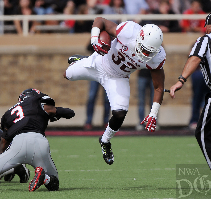 STAFF PHOTO BEN GOFF  @NWABenGoff -- 09/13/14 Arkansas running back Jonathan Williams attempts to recover after taking a hit from Texas Tech defender J.J Gaines during the second quarter of the game in Jones AT&T Stadium in Lubbock, Texas on Saturday September 13, 2014.