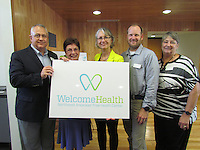 Mark Kidd, president, Susan Chadick, secretary, Monika Fischer-Massie, executive director, Aaron Kribs and Mary Alice Serafini, treasurer, hold a sign with the clinic's new name, Welcome Health.