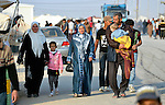 A family walks through the Zaatari Refugee Camp, located near Mafraq, Jordan. Opened in July, 2012, the camp holds upwards of 50,000 refugees from the civil war inside Syria. International Orthodox Christian Charities and other members of the ACT Alliance are active in the camp providing essential items and services.