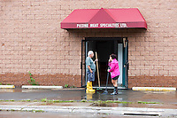 MAMARONECK, NY - AUGUST 28: A cleanup crew works outside of a local business on Jefferson Street in the Village of Mamaroneck, New York on Sunday August 28, 2011 in the aftermath of Hurricane Irene.