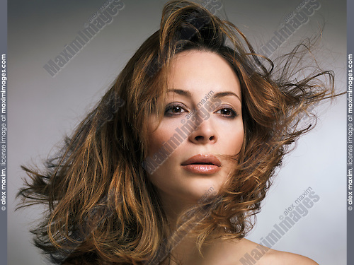 Beauty portrait of a woman with flying light brown hair and natural makeup in her early thirties isolated on gray background