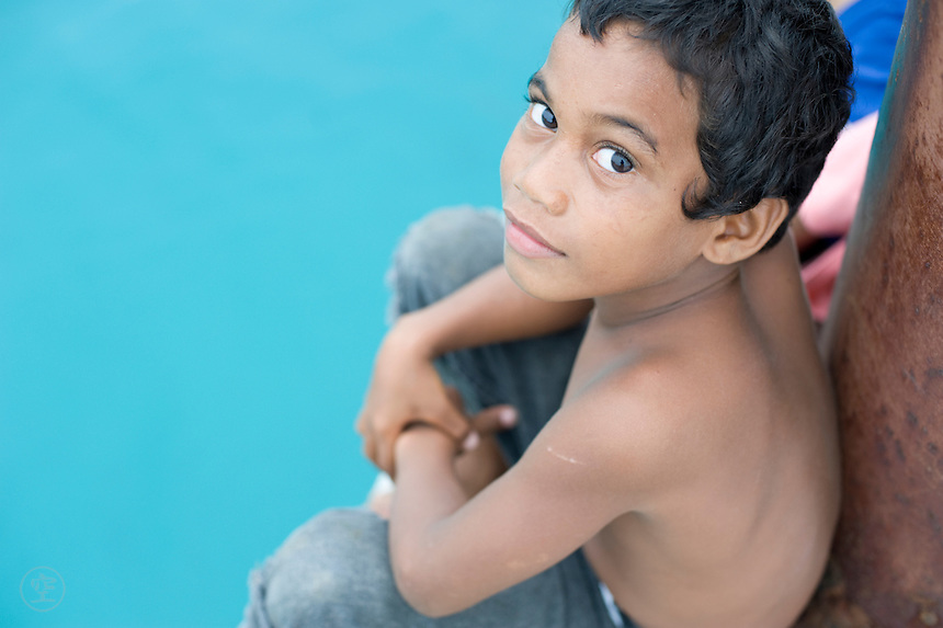 A Marshallese boy sits on the pier at Jabor, Jaluit Atoll, backed by the startling blue-green of the tropical sea.