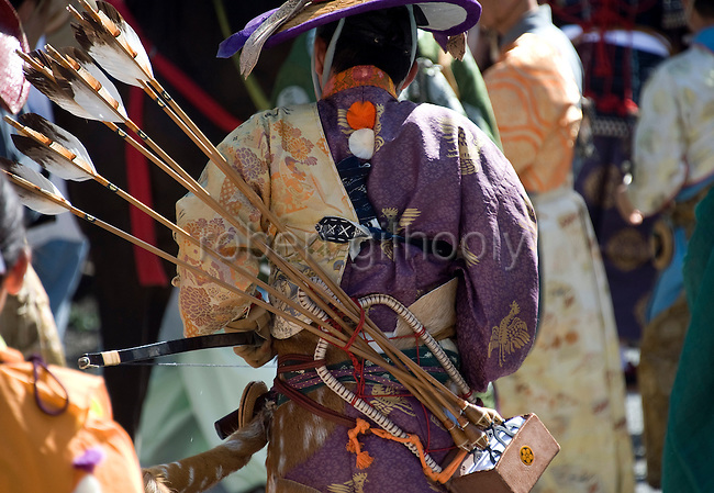 "A participant dressed in traditional attire carries his arrows on his back as he heads toward the start of the ""yabusame-shinji"" mounted archery ritual on the 3-day Reitaisai grand festival in Kamakura, Japan on  16 Sept. 2012.  In the Azumakagami -- a book of Japanese history covering 87 years from 1180 to 1266 in the Kamakura Era, a hunt and mounted archery event was held on August 15 1187 and it is this in which the shrine's Reitaisai has its roots. For over 800 years since the history and tradition of the event have been continued at the shrine. Photographer: Robert Gilhooly"