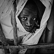 6 year old Abdi Isan peeps through a tent in the Dagahaley refugee camp in the Dadaab refugee camp in northeastern Kenya. Hundreds of thousands of refugees are fleeing lands in Somalia due to severe drought and arriving in what has become the world's largest refugee camp. Photo: Sanjit Das/Panos