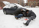 Dan Sua (R) and Casey Scalf put chains on co-workers car after a snowstorm hit the Seattle area early Wednesday morning dumping at least 4 to six inches and will likely continue into the afternoon it a tough commute for drivers  in Seattle on January 18, 2012.  ©2012. Jim Bryant Photo. All Rights Reserved.
