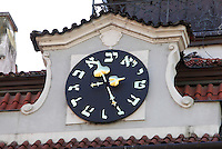 Clock on the Jewish Town Hall or zidovska radnice with Hebrew numerals, which are the same as letters in the Hebrew alphabet. The Hebrew numerals begin with aleph and continue counterclockwise around the clock dial. The Jewish Town Hall was built next to the Old New Synagogue on the corner of Maiselova and Cervena Ulice in 1586 in Renaissance style under the sponsorship of Mayor Mordechai Maisel, with a Rococo facade added in the 18th century, in the Josefov or Jewish quarter of Prague, Czech Republic. The historic centre of Prague was declared a UNESCO World Heritage Site in 1992. Picture by Manuel Cohen