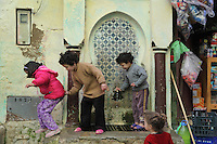 Children playing at an old street fountain in Moulay Idriss, Meknes-Tafilalet, Northern Morocco. The town sits atop 2 hills on Mount Zerhoun and was founded by Moulay Idriss I, who arrived in 789 AD and ruled until 791, bringing Islam to Morocco and founding the Idrisid Dynasty. It is an important pilgrimage site for muslims. Picture by Manuel Cohen