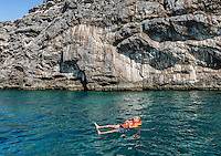 Man enjoys the aquamarine waters off the island of Capri, Naples, Italy