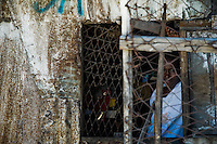 A Haitian woman looks through the wired window in the slum of Cité Soleil, Port-au-Prince, Haiti, 11 July 2008. Cité Soleil is considered one of the worst slums in the Americas, most of its 300.000 residents live in extreme poverty. Children and single mothers predominate in the population. Social and living conditions in the slum are a human tragedy. There is no running water, no sewers and no electricity. Public services virtually do not exist - there are no stores, no hospitals or schools, no urban infrastructure. In spite of this fact, a rent must be payed even in all shacks made from rusty metal sheets. Infectious diseases are widely spread as garbage disposal does not exist in Cité Soleil. Violence is common, armed gangs operate throughout the slum.