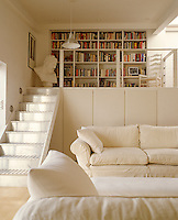 Cupboards have been built under the mezzanine library in this comfortable loft living room