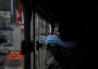 A Filipino man rides the bus in Manila, Philippines..**For more information contact Kevin German at kevin@kevingerman.com