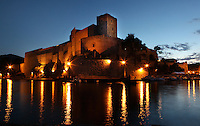 Chateau Royal, Collioure, France, seen at night with the street lights reflecting in the sea. Much of the castle was built in the 13th and 14th centuries by the Dukes of Roussillon and the Knights Templar. In the 16th century Collioure was under Spanish control and Philip II modernised and reinforced the castle. It was taken by the French in 1659 after which the bastions were built by Vauban (1633-1707). Picasso, Matisse, Derain, Dufy, Chagall, Marquet, and many others immortalized the small Catalan harbour in their works. Picture by Manuel Cohen.