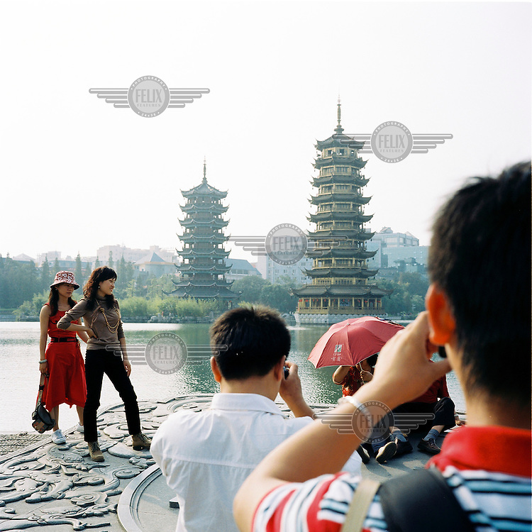 Tourists take pictures on the banks of the river in front of traditional style buildings in Guilin.