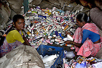 Girls peeling off the labels from shampoo bottles on 12th Dec 2006. The bottles will then be sorted by colour and ground up into small pieces. From there the pieces are dyed then melted and moulded into plastic sheets ready to sell.