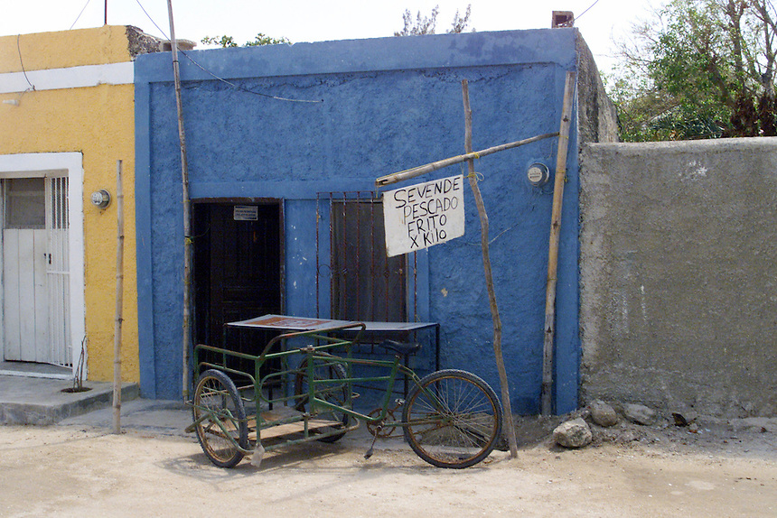 Bicycle cart in from of small blue building in Yucatan Peninsula, Mexico.