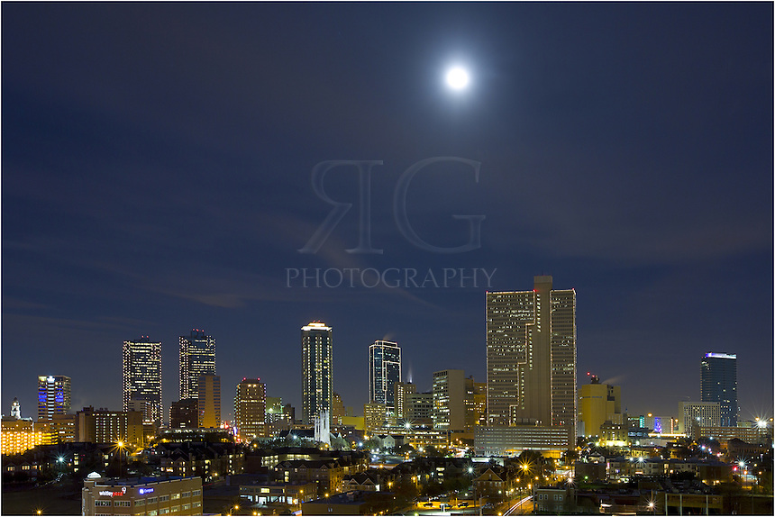 On a cold December day, the moon rises over the high rises and architecture of downtown Fort Worth, Texas.