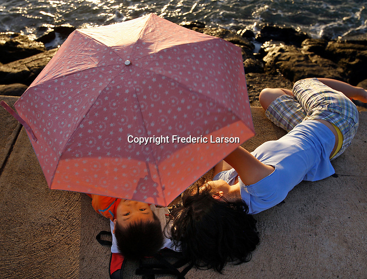 Under an umbrella shield from the sunset in Honolulu in Hawaii,