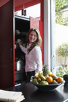 Owner Sarah Russo reaches for a mug from her built-in red lacquered kitchen cupboard
