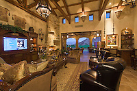 Rustic but luxurious living room features stone inlaid walls , beamed ceilings, wrought iron accents , and clerestory windows