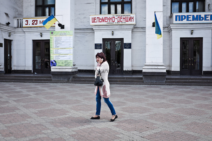 UKRAINE, Mariupol: A woman is walking in front of the Theater right at the center of Mariupol. On the Theater building, we can notice Ukra