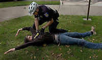 Sacramento police officer Ethan Zeek detains a demonstrator with his taser when he got in his way of a pursuit of another demonstrator after a melee at the anti-Minutemen demonstration on the west side of the State Capitol. The man was not arrested on October 29, 2005.