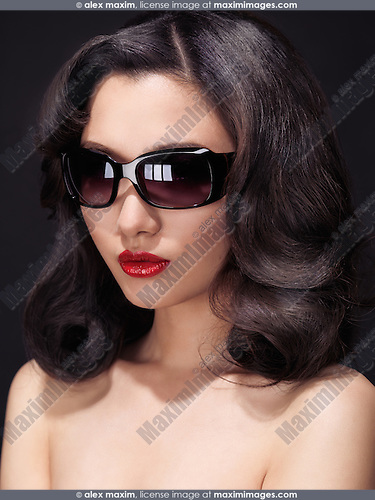 Beauty portrait of a glamorous young woman with red lipstick wearing dark sunglasses