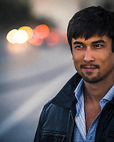 portrait of a handsome Asian American man on a road at dusk
