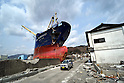 April 1st, 2011, Kamaishi, Japan - A small van goes by the looming bow of Asia Symphony, a Panamanian ocean going vessel being left aground on the wharf in the port of Kamaishi , Iwate Prefecture, on April 1, 2011, three weeks after this major northeastern Japanese port was destroyed by a magnitude 9.0 earthquake and ensuing tsunami. (Photo by Natsuki Sakai/AFLO) [3615] -mis-...