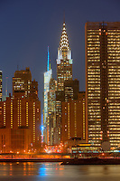 The Bank of America Tower, Chrysler building, and United Nations Secretariat building on 42nd Street, along with other Manhattan buildings at twilight.