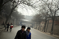 Two chinese girls walking in the streets of Lanzhou near railways where passes a train bringing coal to the major electric factory Guo Jian, witch uses it as energy source.<br /> China.<br /> <br /> <br /> -------<br /> Lanzhou, in the Gansu province is the most polluted cities of China and in the world's top ten for atmospheric pollution due to human activity. The town is situated between two hills along the Yellow River and the polluted clouds remain blocked over the town. The sky is most of the time hidden by the pollution.