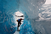 Hiker climbs through tunnel in melting Mendenhall Glacier in Southeast Alaska.<br />