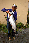 Alaska: Anchorage. Man with salmon. Photo akanch106..Photo copyright Lee Foster, 510/549-2202, lee@fostertravel.com, www.fostertravel.com