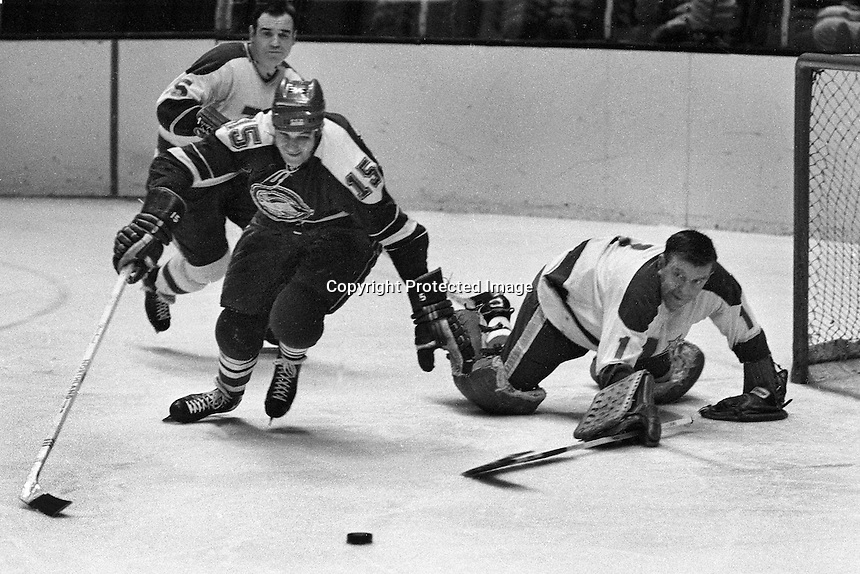 Minnesota's Gump Worsley pokes the puck away from the Seals Mike Laughton. Leo Boivin behind. (Photo copyright 2014 Ron Riesterer)