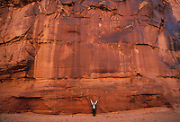 Big red rock walls loom over a visitor to Horseshoe Canyon, Canyonlands National Park, Utah.