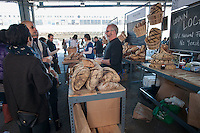 """Customers shop at Orwasher's Bakery at the New Amsterdam Market on South Street in New York during the market's opening day for the season, Sunday, April 29, 2012. The market, located in the former Fulton Fish Market, features vendors who source their artisanal food directly from local farmers and stands of the farmers'  themselves . For opening day they promoted their """"Bread Pavilion"""" which had booths from 16 local artisanal bakeries. (© Richard B. Levine)"""