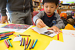 Ethan Lang of Los Altos decorates a book with a sticker during SFMOMA's Family Art Day at Linden Tree Books in Los Altos.