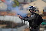 Israeli soldiers fire tear gas at Palestinian protesters during a demonstration against the Prawer plan at the gate of the Beit El settlement, near Ramallah, on November 30, 2013. The so-called Prawer-Begin Bill calls for the relocation of 30,000-40,000 Bedouin, the demolition of about 40 villages and the confiscation of more than 700,000 dunums (70,000 hectares) of land in the Negev. Photo by Issam Rimawi