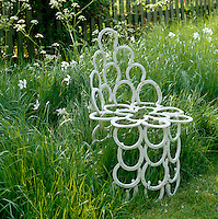 A white chair fashioned out of discarded horseshoes sits amongst the tall grass in this English garden