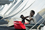 Sentia Fabien, a 10-year old survivor of Haiti's devastating January 12 earthquake, washes laundry outside her family's tent in a displaced person's camp in the Belair section of Port-au-Prince.
