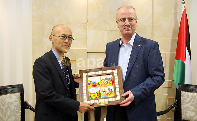Palestinian Prime Minister Rami Hamdallah honors the representative of Japan to Palestine Junya Matsuura, in the West Bank city of Ramallah on May 24, 2015. Photo by Prime Minister Office