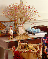 A small china figurine of Father Christmas is displayed on a side table next to an arrangement of beaded decorations