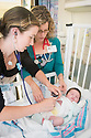 Sarah Gardner, left, class of 2015, examins a three-month-old girl as Karen Leonard, M.D. looks on, at the Vemont Children's Hospital at Fletcher Allen Health Care. Patient release 20130723004.