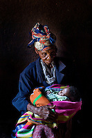 94 year old Golidem holds her one year old great grandson Nhkosina in a small hut in rural Zimbabwe.