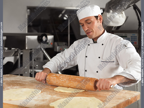 Baker rolling out dough with a rolling pin in a bakery