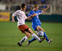 Chelsea Stewart (19) of UCLA is tackled by Kate Norbo (2) of Virginia during the Women's College Cup semifinals at WakeMed Soccer Park in Cary, NC. UCLA advance on penalty kicks after typing Virginia, 1-1 in regulation time.