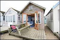 BNPS.co.uk (01202 558833)<br /> Pic: Denisons/BNPS<br /> <br /> Still on the market for &pound;250,000...<br /> <br /> A beach hut on a sandy spit has sold for a whopping &pound;275,000 - and it doesn't even face the sea.<br /> <br /> The small timber cabin can only be slept in for part of the year and the new owners will have to share communal bathroom facilities.<br /> <br /> But the sky-high price tag is down to its location on the exclusive Mudeford Spit in Christchurch, Dorset, which is home to the most expensive beach huts in the country.<br /> <br /> The agents have another hut for sale for &pound;250,000 which is on the beach side of the spit. It also sleeps four to six people and has a mezzanine floor, kitchen area and sun deck.
