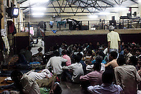 Men watch television during the night shift at the Aashray Adhikar Abhiyan (AAA) Activity Center for homeless people on 4th October 2010, in Old Delhi, India. Picture: Suzanne Lee for The Australian.