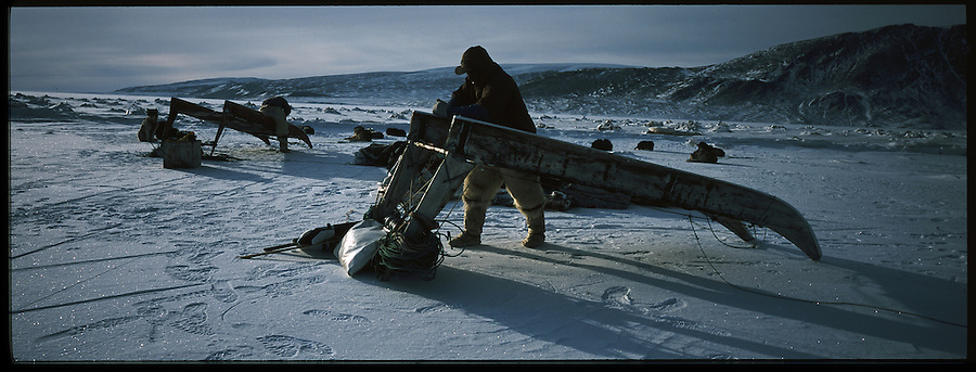 After a long day moving across on often rocky trail through, two hunters plane smooth the runners of a sled to help it run faster across the sea ice the next day. A changing climate - which shows itself in warming temperatures, earlier summers, later winters, and shrinking and thinning sea ice - threatens the livelihoods and traditions of some of the last subsistence hunters on Earth, the Polar Inuit communities of far Northwest Greenland.