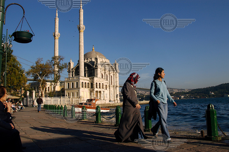 Two young women friends, one wearing a headscarf, on the waterfront of the Bosphorus at Ortakoy. Behind is the mosque of Buyuk Mecidiye, with Asia lying on the far side of the waterway.