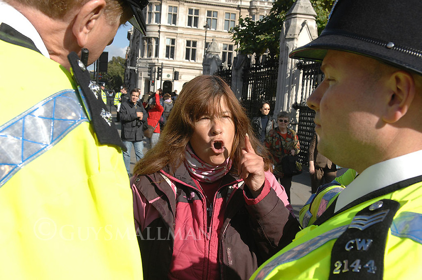 Anti war activist  Barbara Tucker argues with Police outside Parliament, Westminster, London.